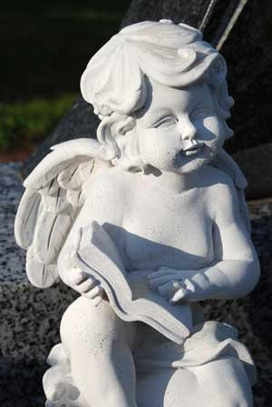 Stauette of a cherub reading a book